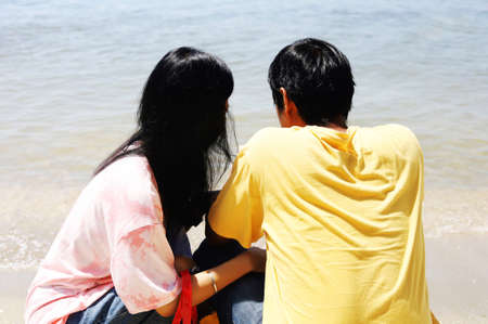 Rear view of sweet couple sitting on the beach for travel, love and Valentine's day concept