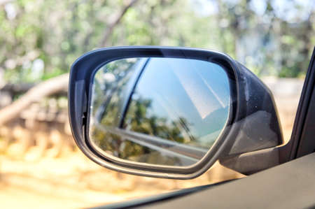 Natural view from car window and side view of black car in wing mirror while driving for transportation concept