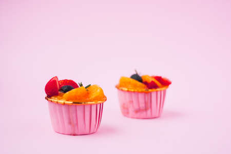 Mini paper cup of fruit or orange sponge cake on pink background for bakery, food and eating concept