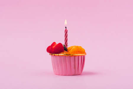 Mini paper cup of fruit or orange sponge cake with burning candle on pink background for birthday  bakery, food and eating concept Imagens