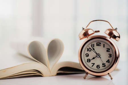 Bell alarm clock and opened book with heart shaped page on the table for study, work, time management and love concept