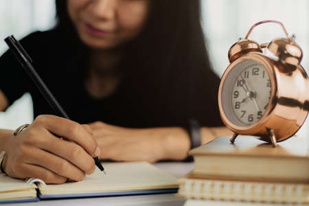 Asian woman writing on a notebook with bell alarm clock on books for study, work and time management concept