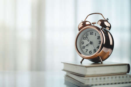 Bell alarm clock on books with copy space for time management for study and work concept