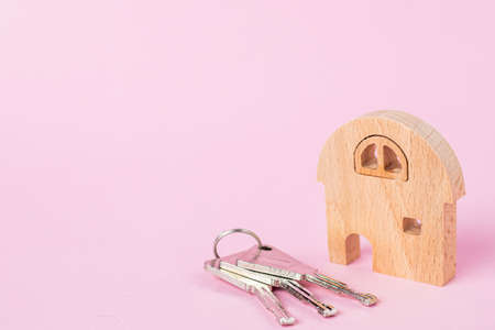 Wooden house model with keys on soft pink background for housing and property concept Imagens