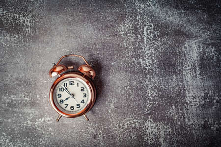 Vintage bell alarm clock on grunge background with copy space for time management concept