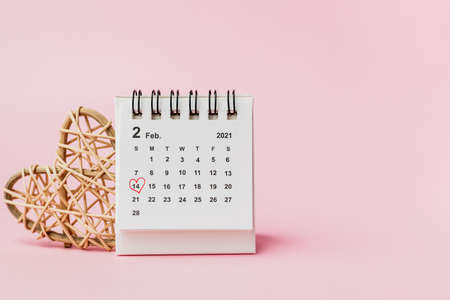Calendar with red heart shaped marking on date February, 14 and wooden wicker heart against pink background for Valentine's day and love concept Imagens