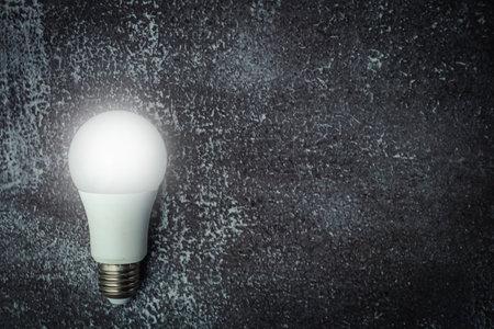 Glowing LED light bulb on dark grunge background for energy savings concept Imagens