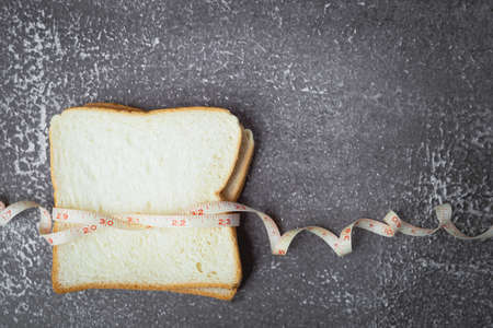 Sliced bread with measure tape on dark grunge background for food and healthy eating concept