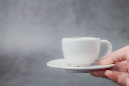Hand holding white cup of coffee with saucer with copy space on dark background for drinks and beverage concept
