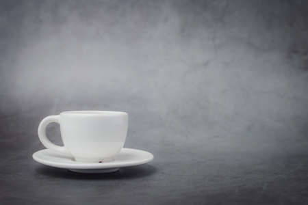 White cup of coffee with saucer with copy space on dark background for drinks and beverage concept