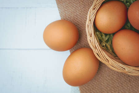 Eggs in the wicker basket on white wooden background for healthy food concept Imagens