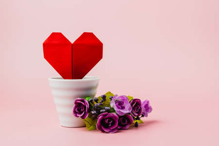 Red paper heart in white flower pot with purple rose bouquet on pink background for love and Valentine's day concept