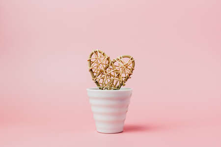 Wooden wicker heart in white flower pot on pink background for love and Valentine's day concept Imagens