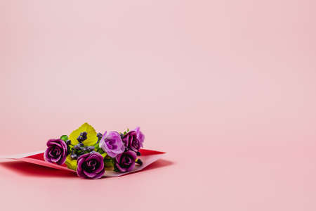 Artificial purple rose bouquet in pink envelope against pink background for Valentine's day and love concept