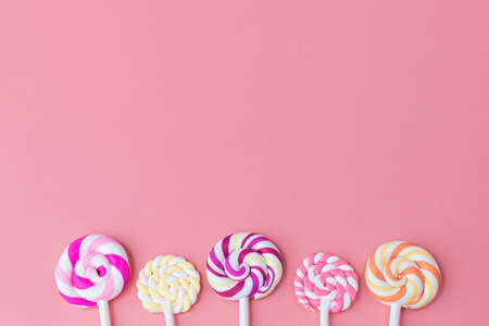 Delicious colourful of lollipop on pink background with copy space for snack food concept