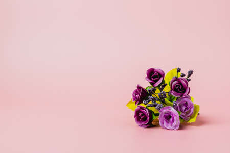 Artificial purple rose bouquet on pink background for love and Valentine's day concep