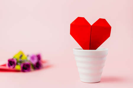 Red paper heart in white flower pot with blurred purple rose bouquet on pink background for love and Valentine's day concept