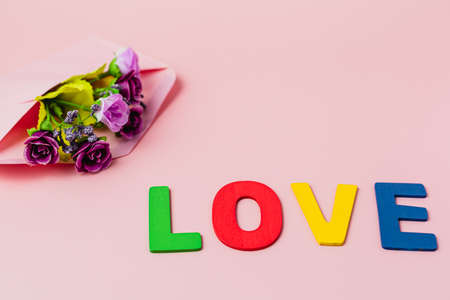 LOVE word with artificial purple rose bouquet in envelope on pink background for love and Valentine's day concept