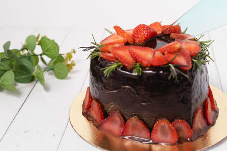 A plastic knife cutting onto the delicious chocolate cake with strawberries on white background for food and bakery concept