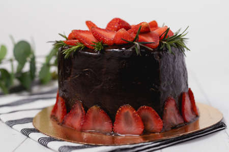 Delicious chocolate cake with strawberries on white background for food and bakery concept
