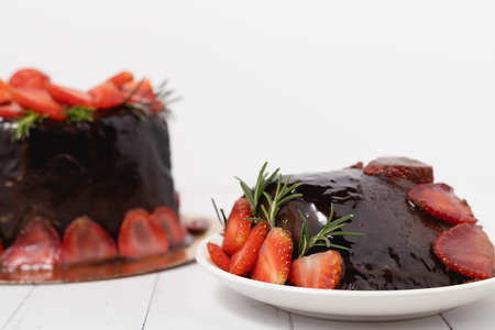 A piece of delicious chocolate cake with strawberries on white background for food and bakery concept