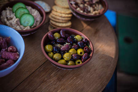 Olives in a Wooden bowl on a wooden table
