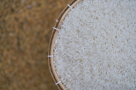 Close-up of grains of uncooked white  jasmine rice in  bamboo container . Jasmine rice is grown primarily in Thailand (Thai hom mali or Thai fragrant rice) Reklamní fotografie