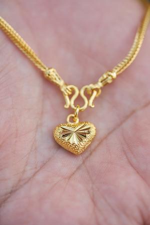 gold jewelry in lady hands.heart shape for girlfriend on Valentines Day. Reklamní fotografie
