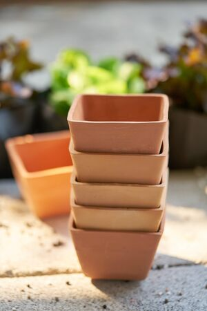 Five orange square clay pots stacked in the garden.