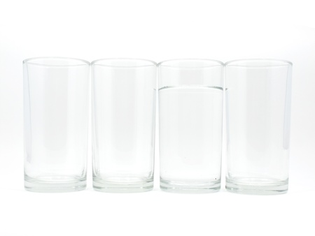 Four glasses with water in one glass on white background Stock Photo
