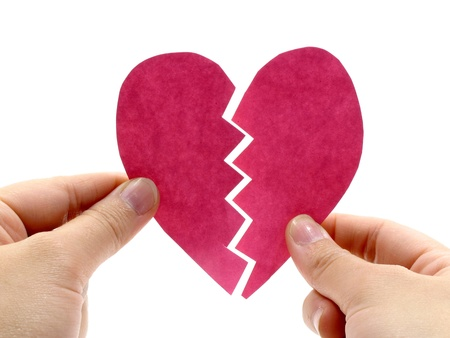 pink heart: Broken pink heart is holding by hand on white background