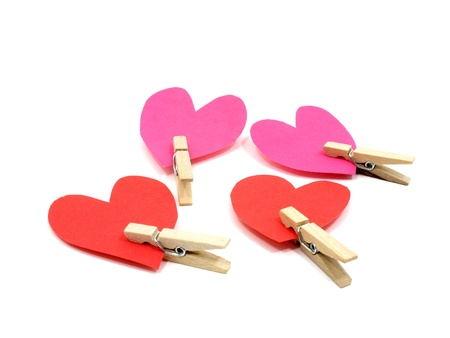 Four hearts with wooden pins on each heart on white background Stock Photo
