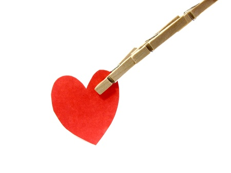 Wooden pins pinch red heart on white background