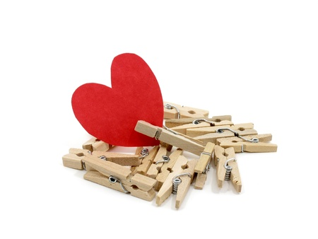 Red heart on many wooden pins with one wooden pin pinch it on white background photo