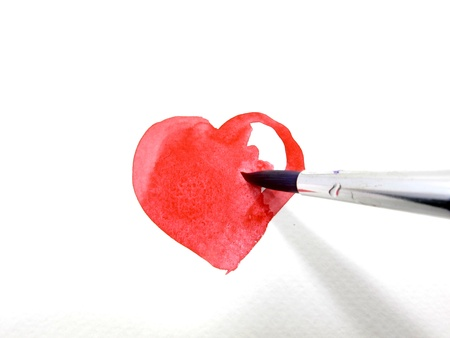 Painting a red heart with water color by paintbrush