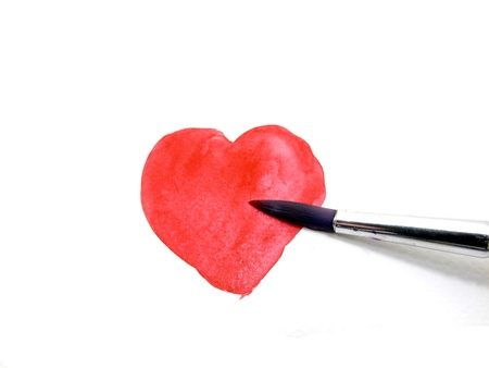 Painting a red heart with water color by paintbrush photo