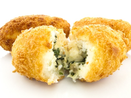 Three croquettes on white background with one is cutting