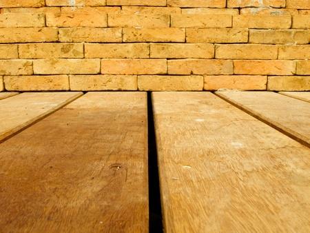Orange brick wall and brown wood floor photo