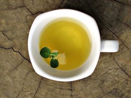 Tea with green leaf in white cup on wood