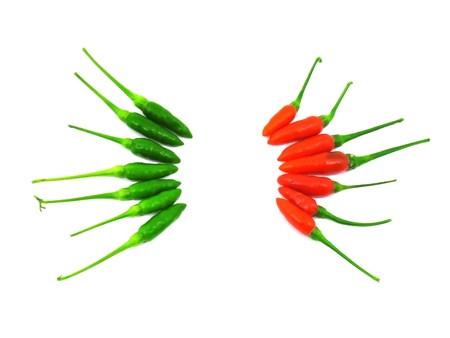 Red and green chili peppers separate in two sides on white background Stock Photo - 13322289