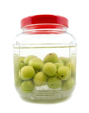 Pickle Japanese plum liqueur in glass jar with rice whiskey and rock sugar isolated