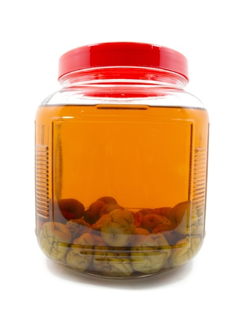 After pickle Japanese plum liqueur in glass jar with rice whiskey and rock sugar isolated photo