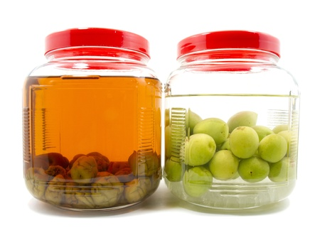 Before and after pickle Japanese plum liqueur in glass jar with rice whiskey and rock sugar photo