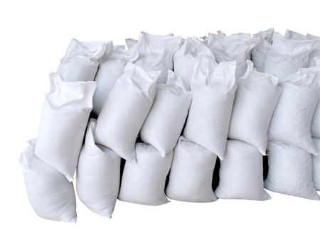 sandbag: Pile of white sacks full with sand and rock isolated