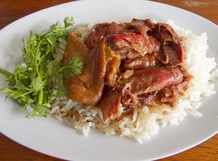 Thai stewed pork leg with rice and parsley  Kao Ka Moo  on white plate