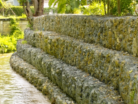 Gabion wall beside stream photo