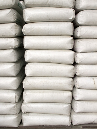 cement pile: Pile of white plastic sacks in warehouse