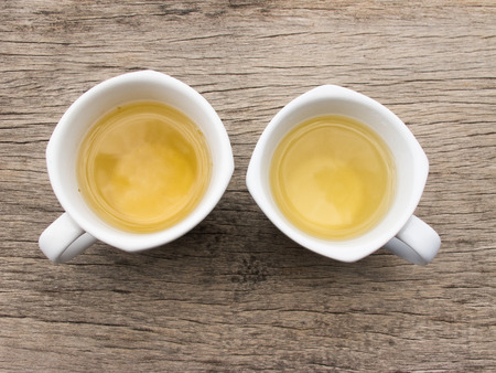 Two white teacup with tea on wood