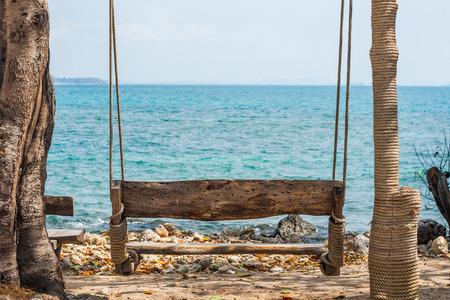 Wood swing on the beach near sea