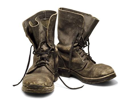 botas: Botas militares viejas y sucias aisladas sobre fondo blanco